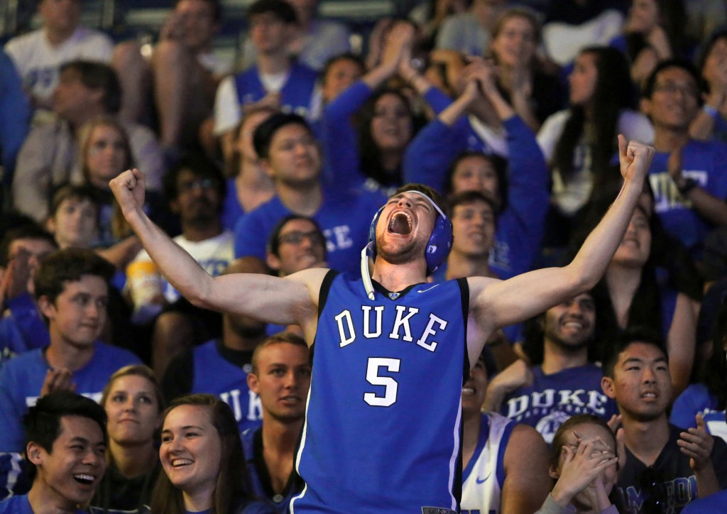 Jack Grady, a Duke sophomore, throws up his arms and celebrates as Duke takes the lead while watching the Final Four of the NCAA basketball championship in Cameron Indoor Stadium at Duke University in Durham, N.C. on Saturday, April 4, 2015. Grady wore his wrestling head gear from high school, which coincidently is also Duke blue.