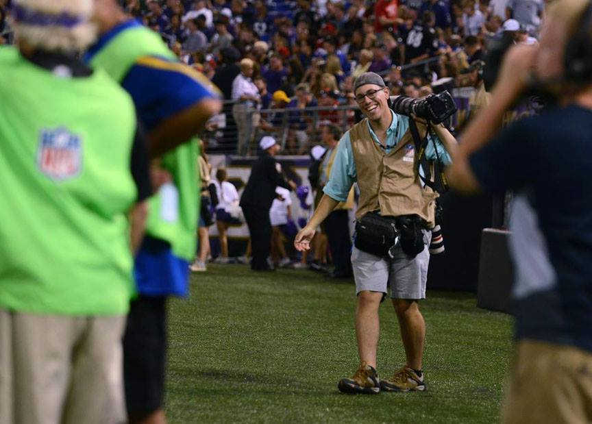 Baltimore Sun photo intern Al Drago dances after making an early deadline at the Baltimore Ravens vs. San Francisco 49ers preseason NFL game in Baltimore, M.D. in August 2014. Photo by Rachel Woolf.