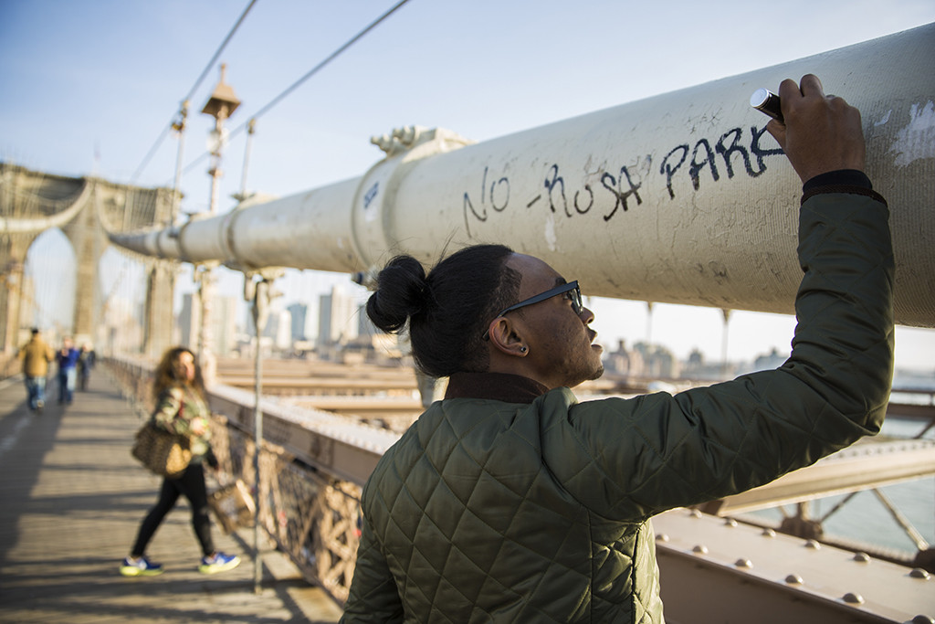 SECOND PLACE: Mark Watkins, Georgia College and State University (Macon McGinley, adviser) — New York native Tajjy Melendez, 21, signs his tagline to the Brooklyn Bridge while his girlfriend Yessinia Paidilla, 19, watches.