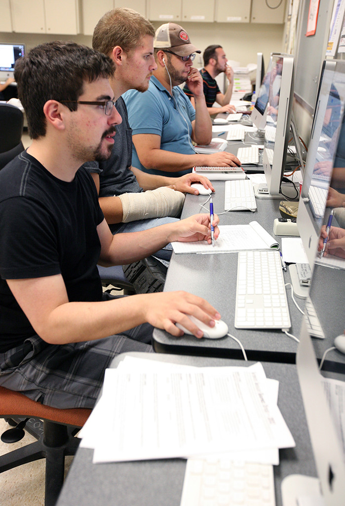 Vinny Vella works on the daily newspaper student produced as part of the Dow Jones News Fund internship workshop at the University of Texas. Photo by Bradley WIlson.
