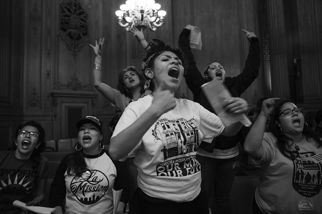 "At nearly midnight on June 2, 2015, Alondra Aragon, center, led a chant in City Hall in San Franciso, Calif. immediately after the Mission Moratorium was voted on. The final vote was 7-4 in favor of the moratorium, but the measure needed nine votes to be passed as an ""interim emergency ordinance."" Aragon and dozens of other Mission Moratorium supporters had filled the room for over eight hours that day. Of the supporters, San Francisco Board of Supervisors Member John Avalos said, ""The rich fabric of the Mission is what is here today."" Katy Tang, the supervisor from District 4, said, ""This was incredibly moving for me, although at times emotional, very inspirational."""