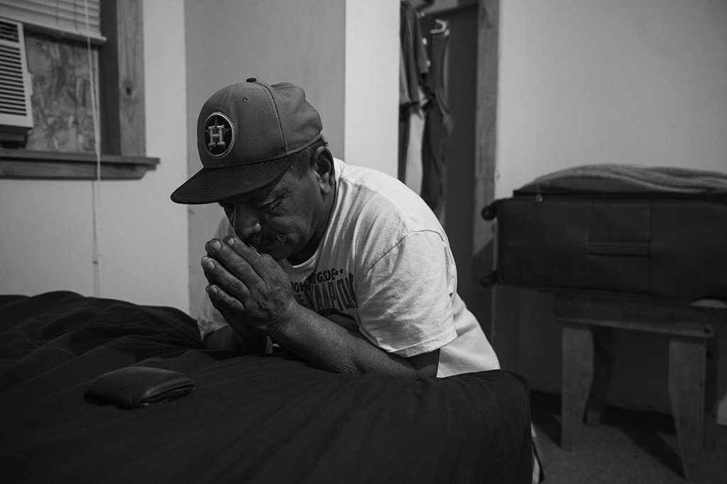 "Tino Gaona prays in his bedroom on the morning of his youngest daughter's 24th birthday, which he is missing because he must work in the oil fields, in Cotulla, Texas, U.S. on August 6, 2015. ""I miss a lot of birthdays and holidays, but that is how it goes,"" he said. He prays every morning before going to work in the oil field. Of God, he said, ""He's the reason I am still here, so I pray for everybody on my crew."""